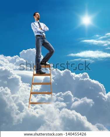 Young confident businessman standing at the top of ladder high in the sky and looking for new opportunities  - stock photo