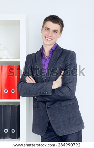young confident businessman standing in his office - stock photo