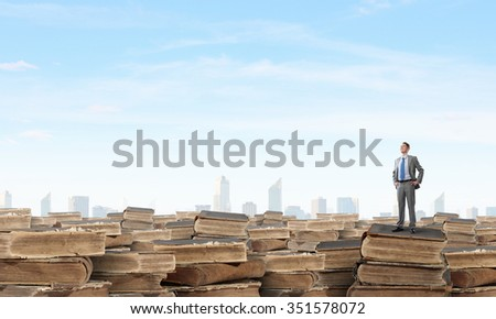 Young confident businessman with arms on waist standing on pile of old books  - stock photo