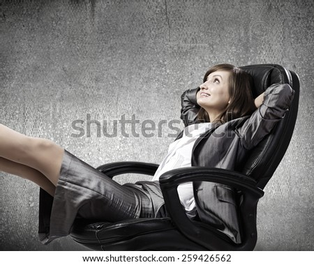 Young confident businesswoman sitting in chair with legs up - stock photo