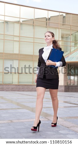 Young confident businesswoman with folder walking near the office building