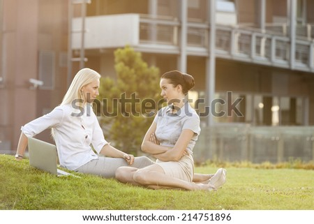 Young confident businesswomen looking at each other in office lawn - stock photo