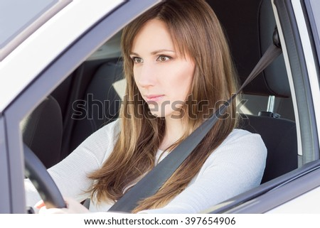 Young confident car driver woman steering wheel. Pretty caucasian girl in the car - stock photo