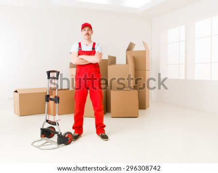 young confident delivery man standing in new home, holding hands crossed against his chest, with cardboard boxes in background - stock photo