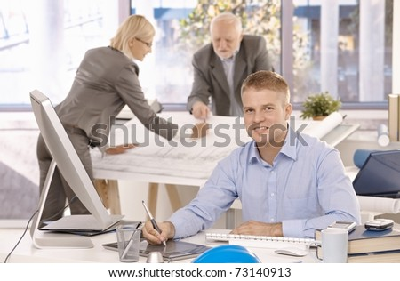 Young confident designer working on drawing pad, looking at camera, smiling, colleagues working in background.? - stock photo