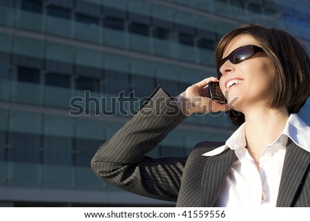 Young confident female professional talking on mobile phone in front of office building - stock photo