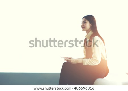Young confident Japanese woman professional is holding smart phone, while is sitting in modern office interior near copy space area background for your information text message or advertising content - stock photo