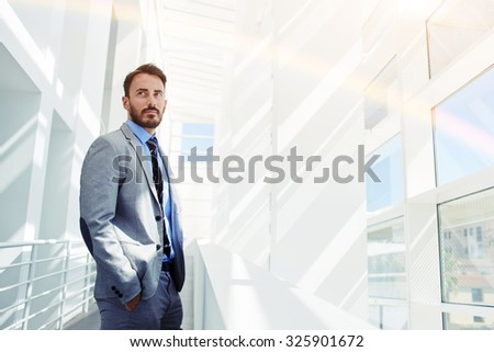 Young confident male ceo dressed in elegant clothes posing while standing in modern office building, successful intelligent man in luxury suit resting after business meeting with his partners  - stock photo