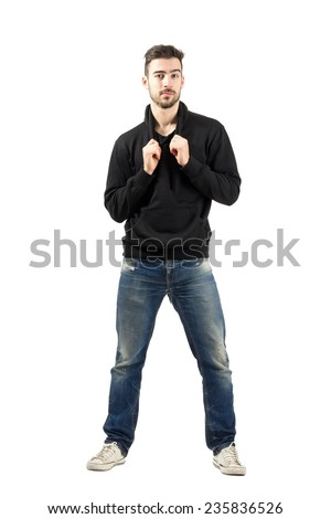 Young confident man pulling hoodie strings looking at camera. Full body length portrait isolated over white background. - stock photo