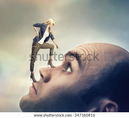 Young confident personal coach is standing on the man's face - stock photo