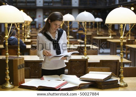 Young confident student standing at desk in old university library studying books. - stock photo