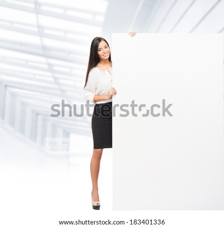 Young, confident, successful and beautiful business woman with the blank billboard - stock photo