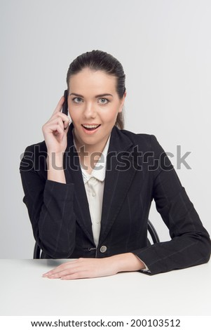 Young, confident, successful, beautiful and surprised business woman with the mobile phone isolated on white - stock photo