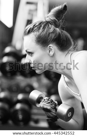 Young confident woman doing biceps curl exercise with dumbbells in fitness center. Slim girl training in the gym with dumbbells. Black and white image