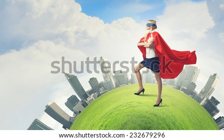 Young confident woman in red cape and mask - stock photo