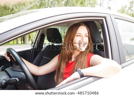 Young confident woman in red dress sitting in the car and holding wheel
