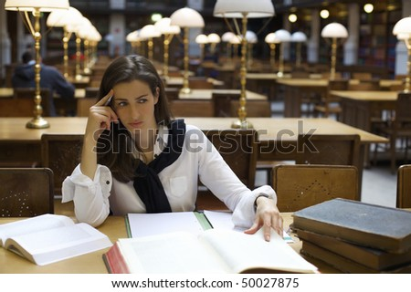 Young confident woman sitting at desk in old university library with books and note pad contemplating. - stock photo