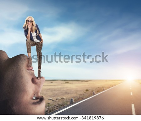 Young confident woman standing on the man's face - stock photo