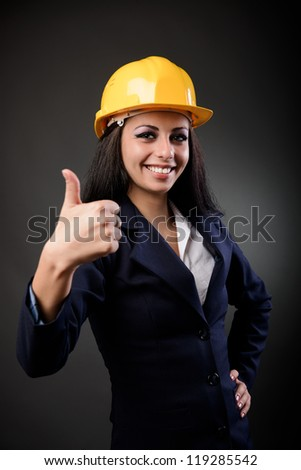 Young construction engineer woman with hardhat making thumbs up sign - stock photo