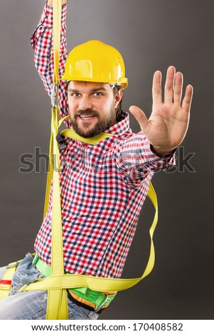 Young construction man with hard hat wearing  a fall protection harness and lanyard for work at heights saluting.Gray background - stock photo