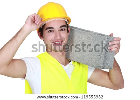 Young construction worker carrying a breeze block. - stock photo