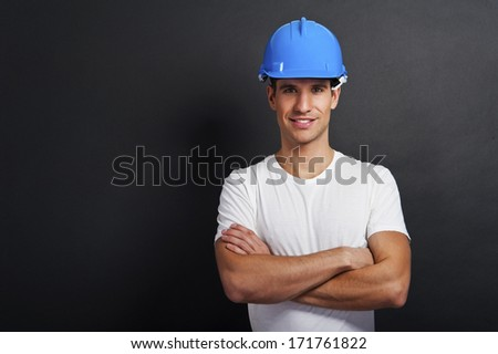 Young construction worker in hard hat on dark background - stock photo