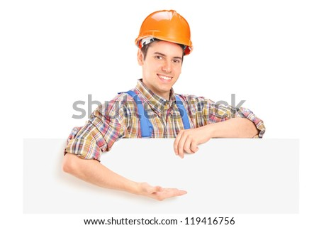 Young construction worker with helmet posing behind a panel and gesturing isolated on white background - stock photo