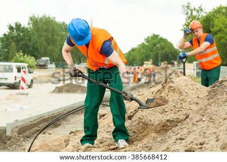 Young construction worker working hard with spade - stock photo