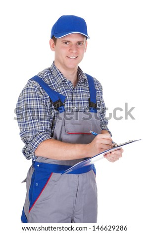 Young construction worker writing on clipboard isolated on white background - stock photo