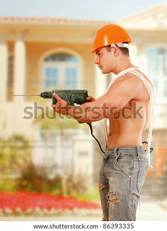 Young constructor/bodybuilderposing with drill outdoors. Side view