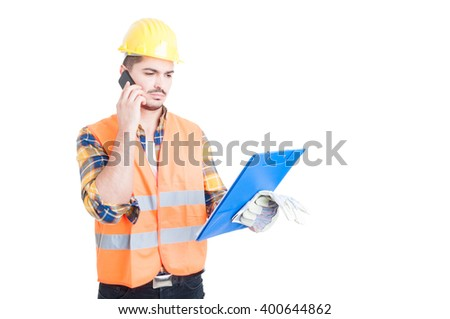 Young constructor holding a clipboard while talking on smartphone isolated on white background - stock photo