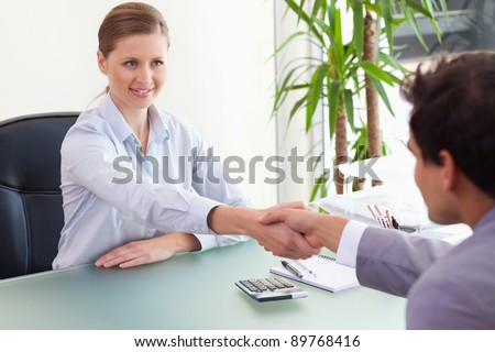 Young consultant shaking hands with her client - stock photo
