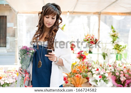 Young consumer woman buying and holding a bouquet of fresh flowers from a floral market stall business and using a smartphone in the store during a sunny day, outdoors. - stock photo