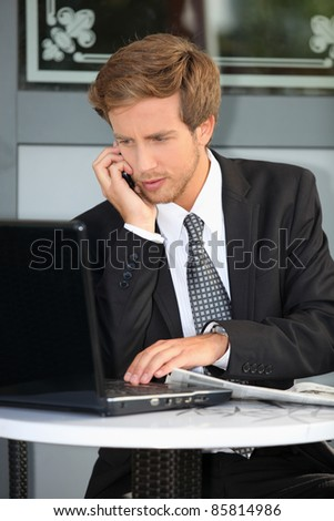 Young contractor with laptop and cell phone - stock photo