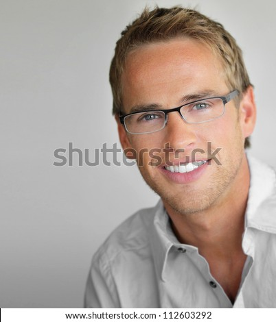 Young cool trendy man with glasses smiling - stock photo