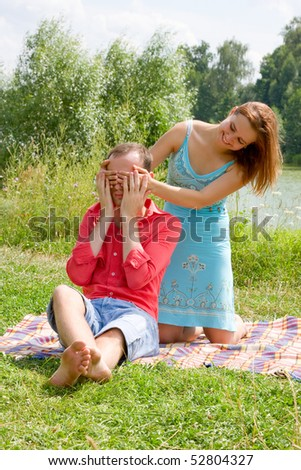 Young cople laying on a blanket on the grass on a hot summer day.  Woman and man are enjoying the sunshine in a park. Just happy couple relaxing. - stock photo