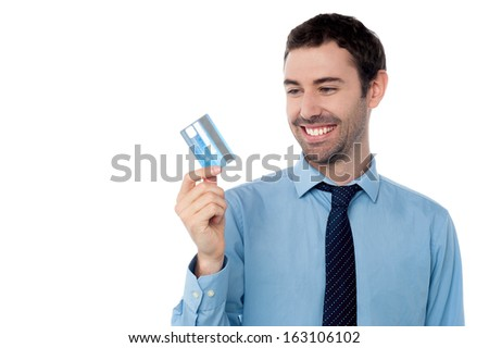 Young corporate guy holding his debit card