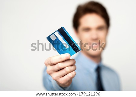 Young corporate guy showing his debit card - stock photo