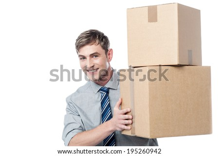 Young corporate man handing pile of cardboard boxes - stock photo