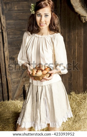 Young country woman with egg basket in the barn