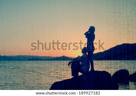 Young couple admiring the sunset on the beach. Filtered image: vintage, grunge and texture effects - stock photo
