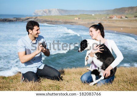Young couple and dog on travel in Asturias coast, Spain. Man taking photo to her girlfriend with retro camera. - stock photo