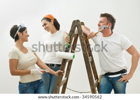 Young couple and friend painting new home, smiling at each other. Isolated on white background. - stock photo
