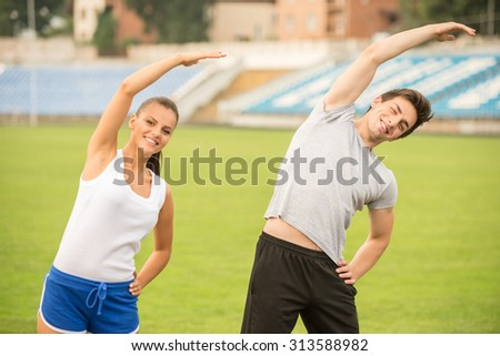 Young couple are doing exercises, stretching on stadium. - stock photo