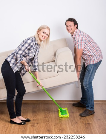 Young couple are doing house cleaning. Smiling and looking at the camera. - stock photo