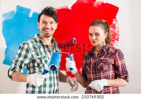 Young couple are doing repair at home and painting a wall with roller. - stock photo