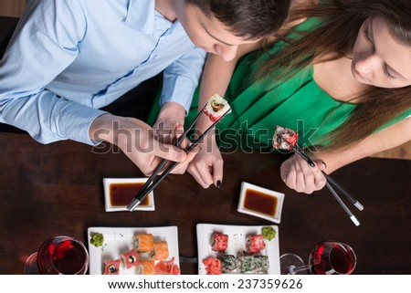 Young couple are eating sushi at restaurant. Top view. - stock photo