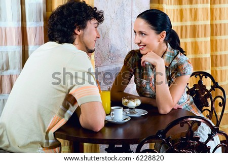 Young couple are sitting at the table and looking at each other - stock photo