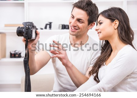 Young couple are using pc tablet to looking at photographs. - stock photo