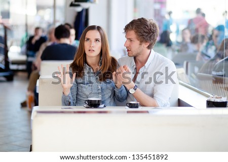 Young couple arguing in a cafe. She's had enough, boyfriend is apologizing. Relationship problems. - stock photo